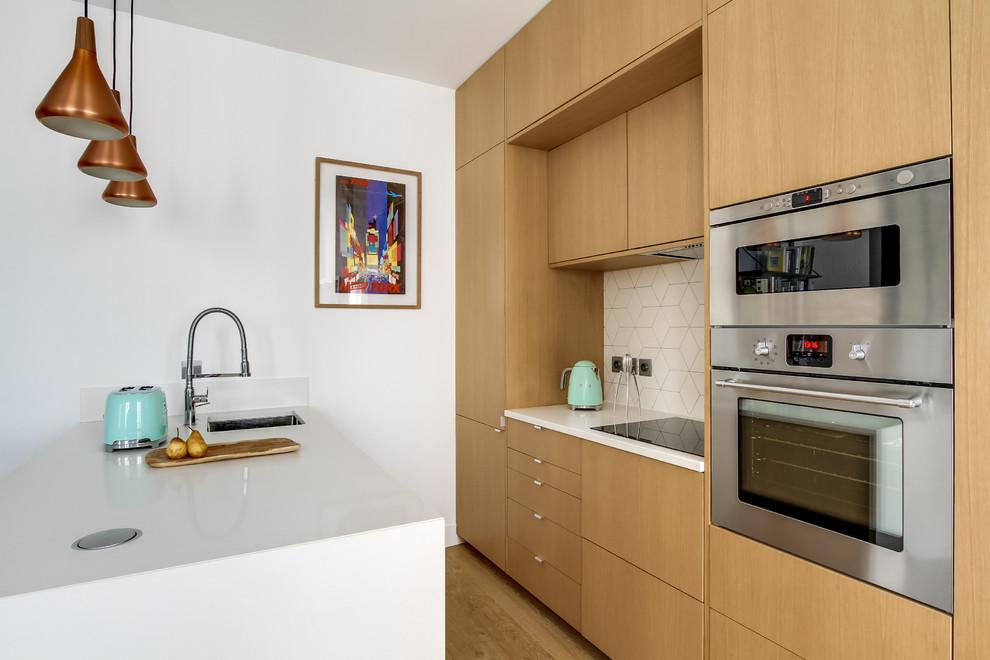 Ispirazione per una piccola cucina contemporanea con lavello sottopiano, ante lisce, ante in legno scuro, paraspruzzi bianco, elettrodomestici in acciaio inossidabile, pavimento in legno massello medio e penisola