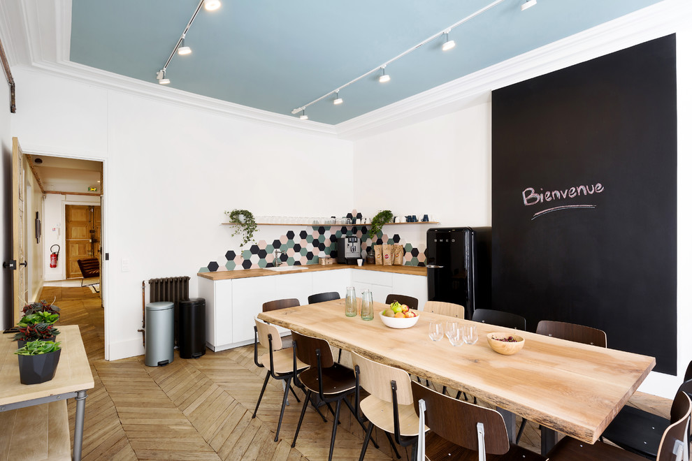 Inspiration for a scandinavian l-shaped light wood floor and beige floor eat-in kitchen remodel in Paris with a drop-in sink, flat-panel cabinets, white cabinets, wood countertops, multicolored backsplash, black appliances, no island and beige countertops