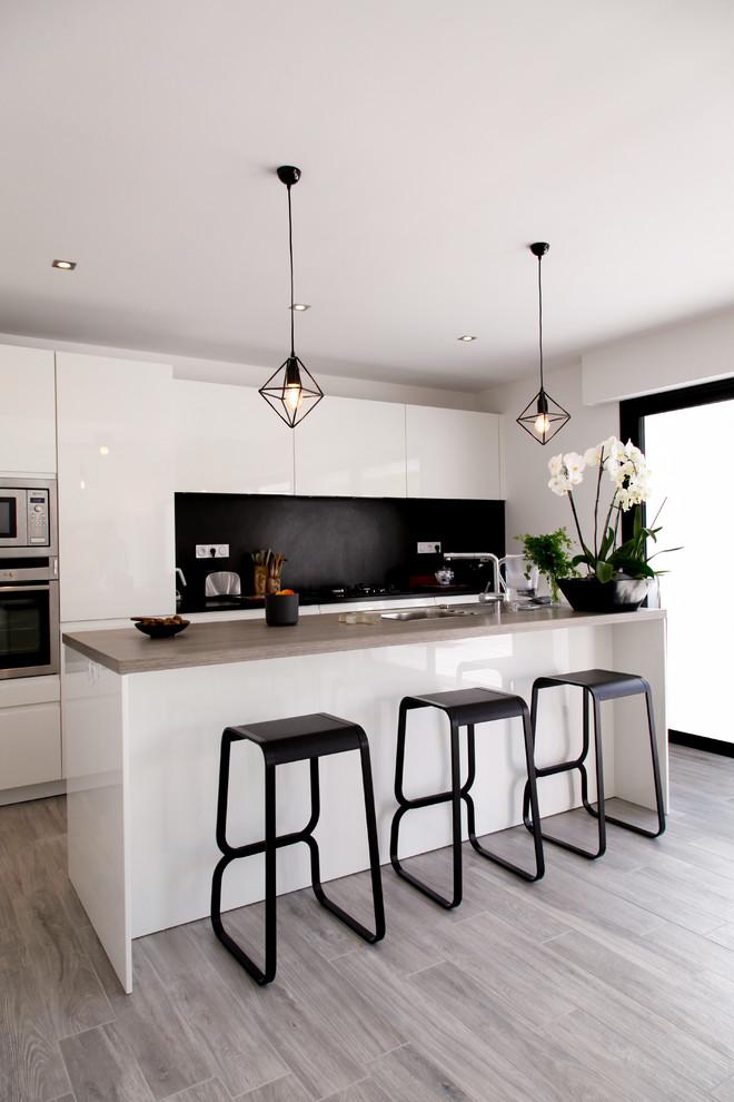 Idee per una cucina a corridoio contemporanea di medie dimensioni con ante lisce, ante bianche, paraspruzzi nero, elettrodomestici in acciaio inossidabile, parquet chiaro e isola