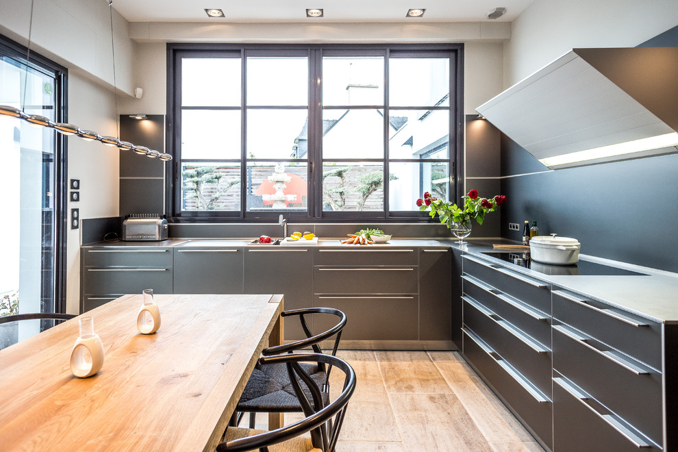 Example of a mid-sized trendy l-shaped medium tone wood floor and brown floor eat-in kitchen design in Brest with flat-panel cabinets, gray cabinets, no island, a single-bowl sink, stainless steel countertops, black backsplash, paneled appliances and gray countertops
