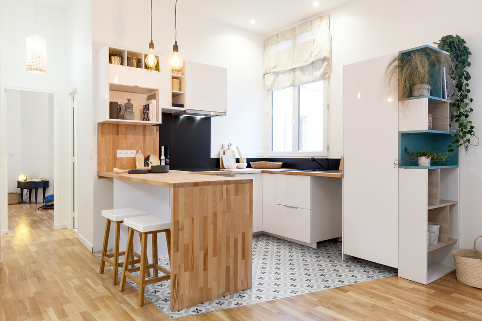 Example of an u-shaped cement tile floor and multicolored floor kitchen design in Paris with flat-panel cabinets, white cabinets, wood countertops, black backsplash and a peninsula