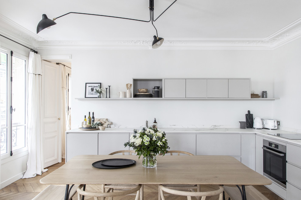 Mid-sized danish l-shaped light wood floor eat-in kitchen photo in Paris with gray cabinets, quartz countertops, white backsplash, black appliances, no island, white countertops and flat-panel cabinets