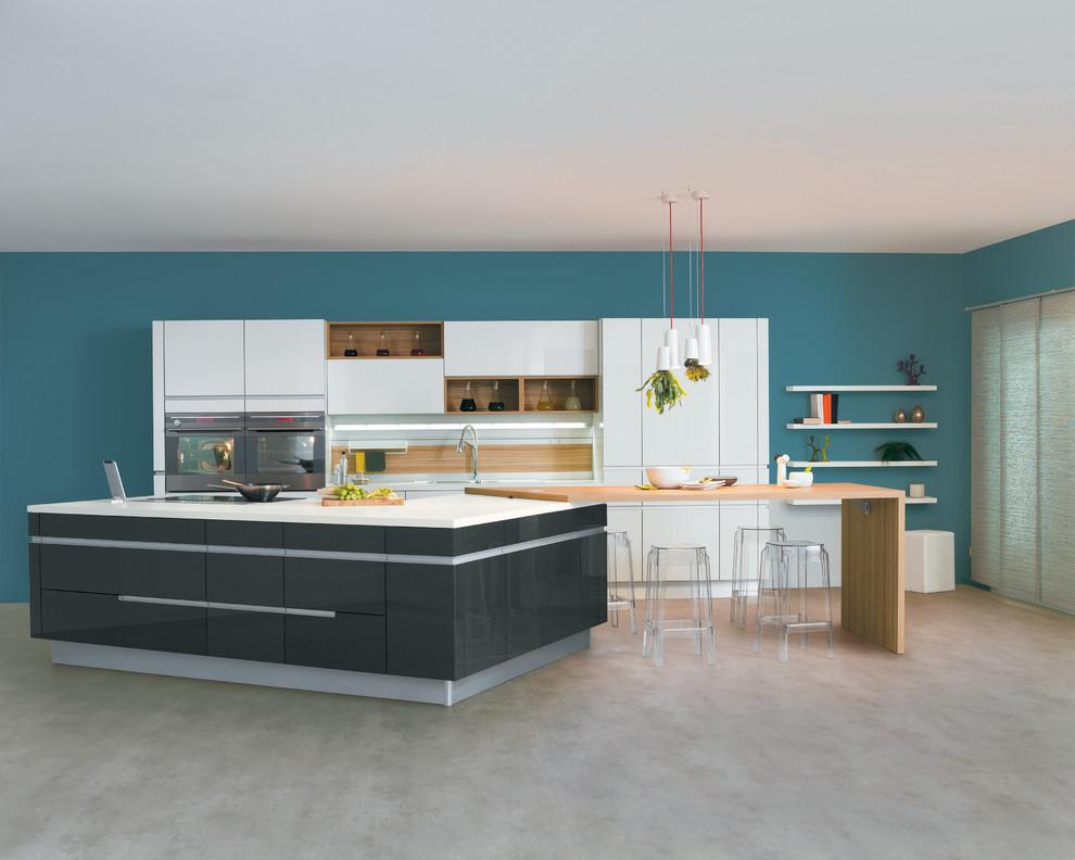 Inspiration pour une grande cuisine ouverte parallèle design avec des portes de placard blanches, une crédence blanche, un électroménager en acier inoxydable et un îlot central.