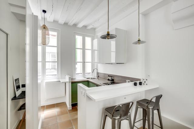 Exemple d'une cuisine scandinave en U fermée avec un évier posé, un placard à porte plane, des portes de placards vertess, un plan de travail en bois, un électroménager noir, une péninsule, un sol beige et un plan de travail marron.