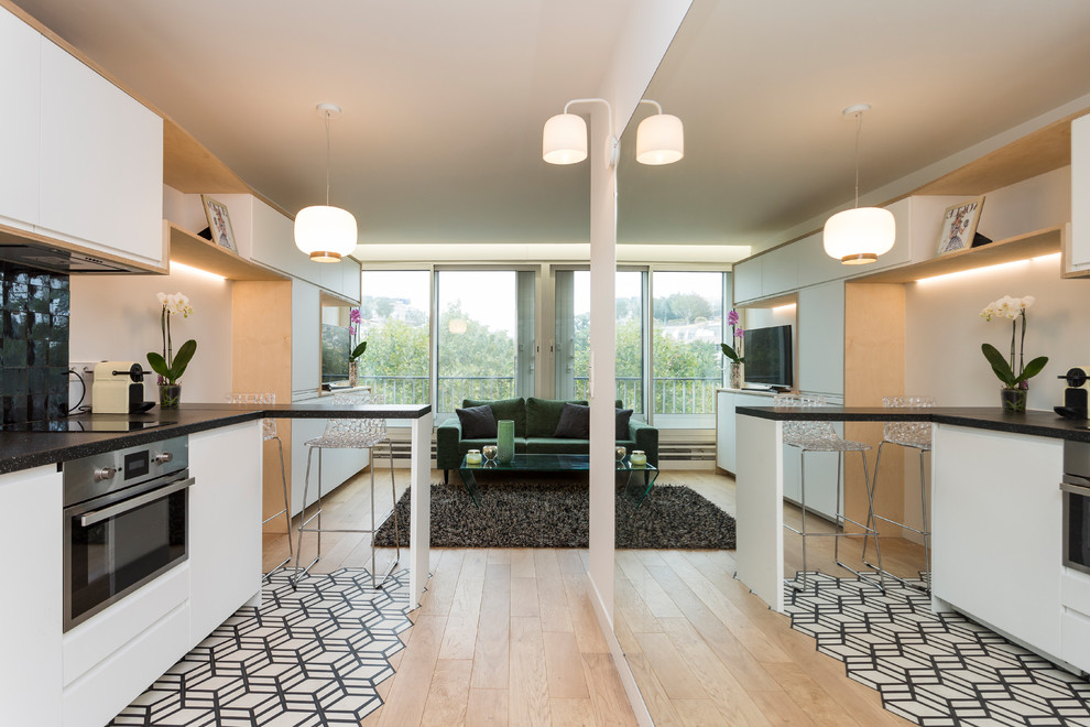 Inspiration for a small scandinavian single-wall cement tile floor and white floor open concept kitchen remodel in Paris with an undermount sink, white cabinets, laminate countertops, black backsplash, terra-cotta backsplash, paneled appliances, no island and flat-panel cabinets