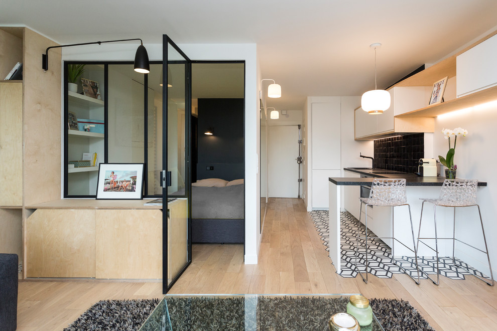 Example of a small danish single-wall cement tile floor and white floor open concept kitchen design in Paris with an undermount sink, white cabinets, laminate countertops, black backsplash, terra-cotta backsplash, paneled appliances, no island and flat-panel cabinets