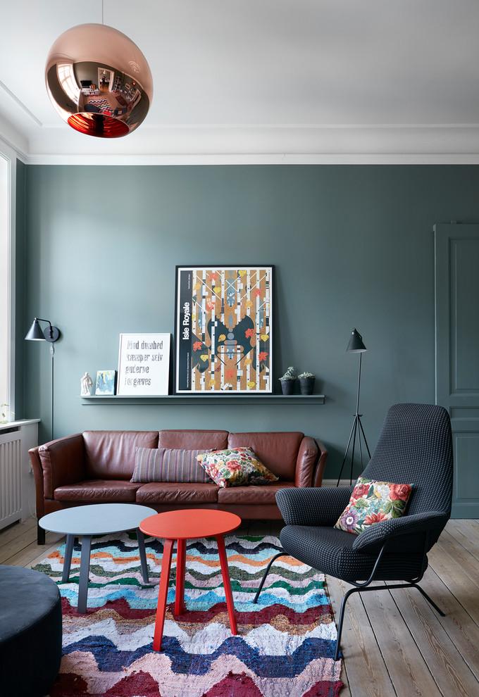 Living room - scandinavian light wood floor and brown floor living room idea in Copenhagen with green walls