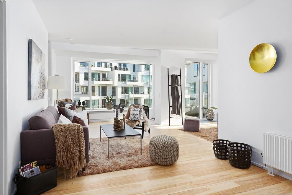 Inspiration for a mid-sized scandinavian open concept light wood floor and brown floor living room remodel in Copenhagen with white walls