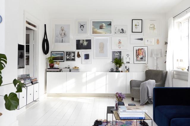 Bild på ett mellanstort skandinaviskt vardagsrum, med vita väggar, målat trägolv och en väggmonterad TV