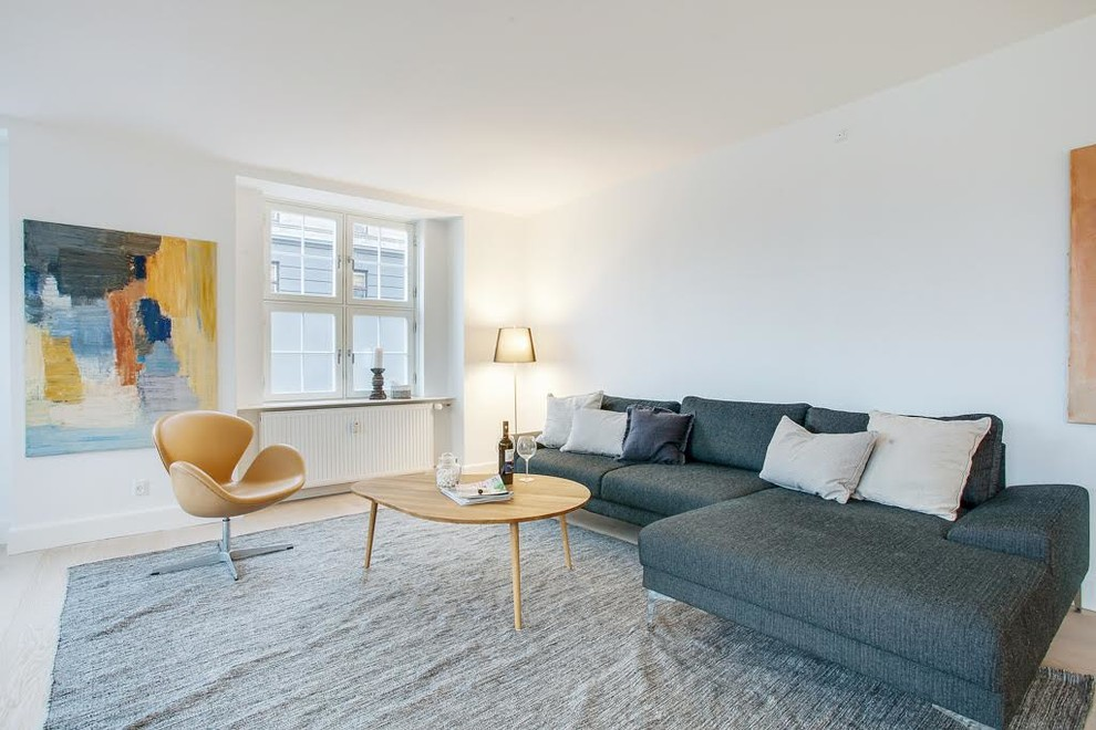 Danish light wood floor living room photo in Copenhagen with white walls, no fireplace and no tv