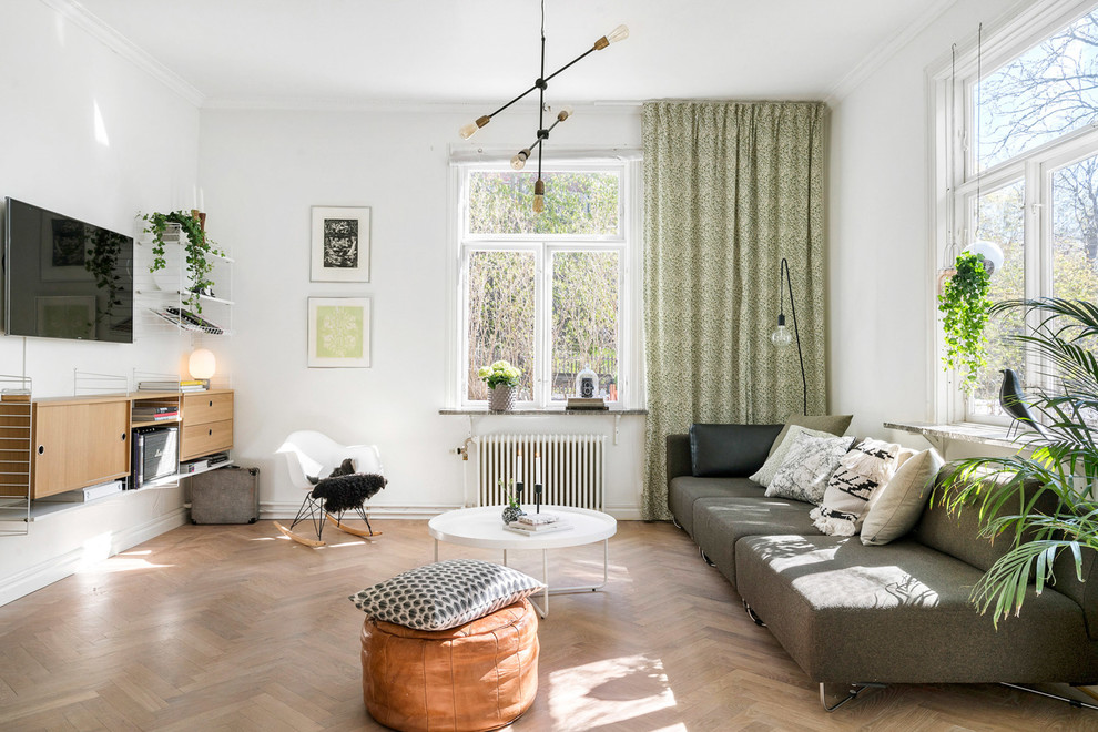 Large danish enclosed medium tone wood floor and brown floor living room photo in Copenhagen with white walls, no fireplace and a wall-mounted tv