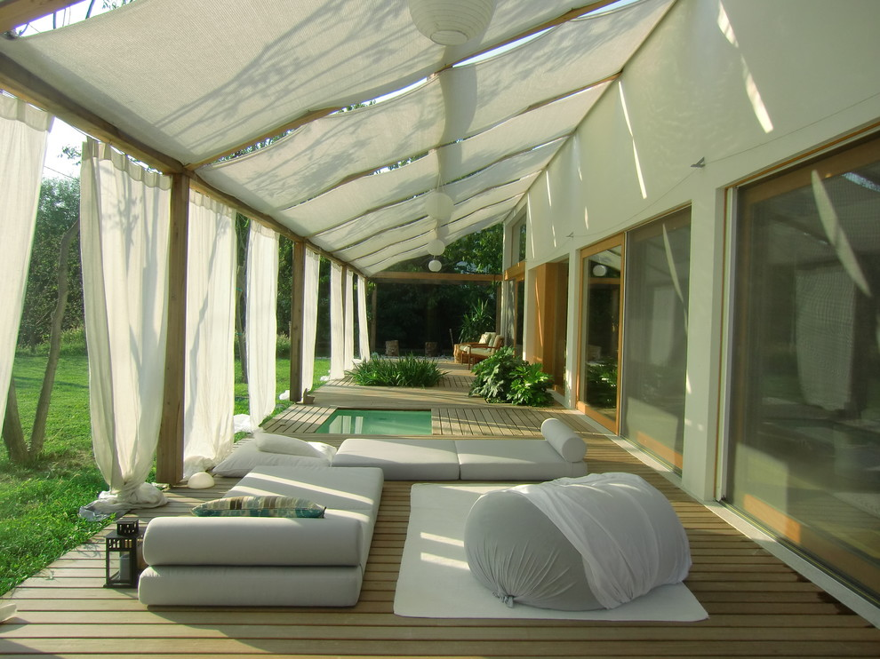 Example of a large minimalist deck design in Miami with an awning
