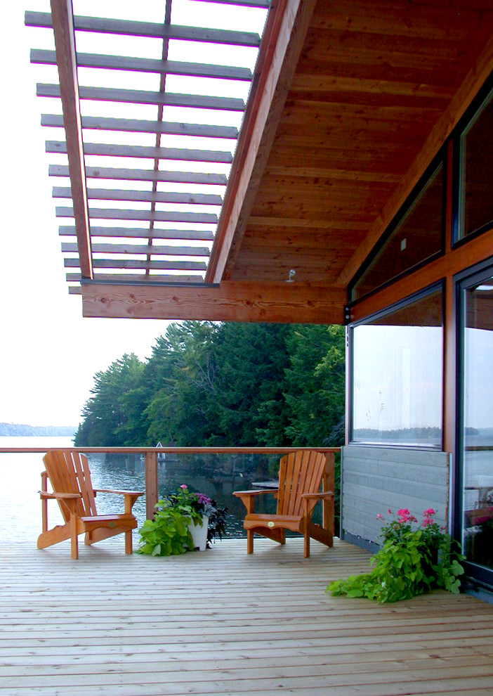 Example of a mid-sized mountain style deck container garden design in Toronto with a roof extension