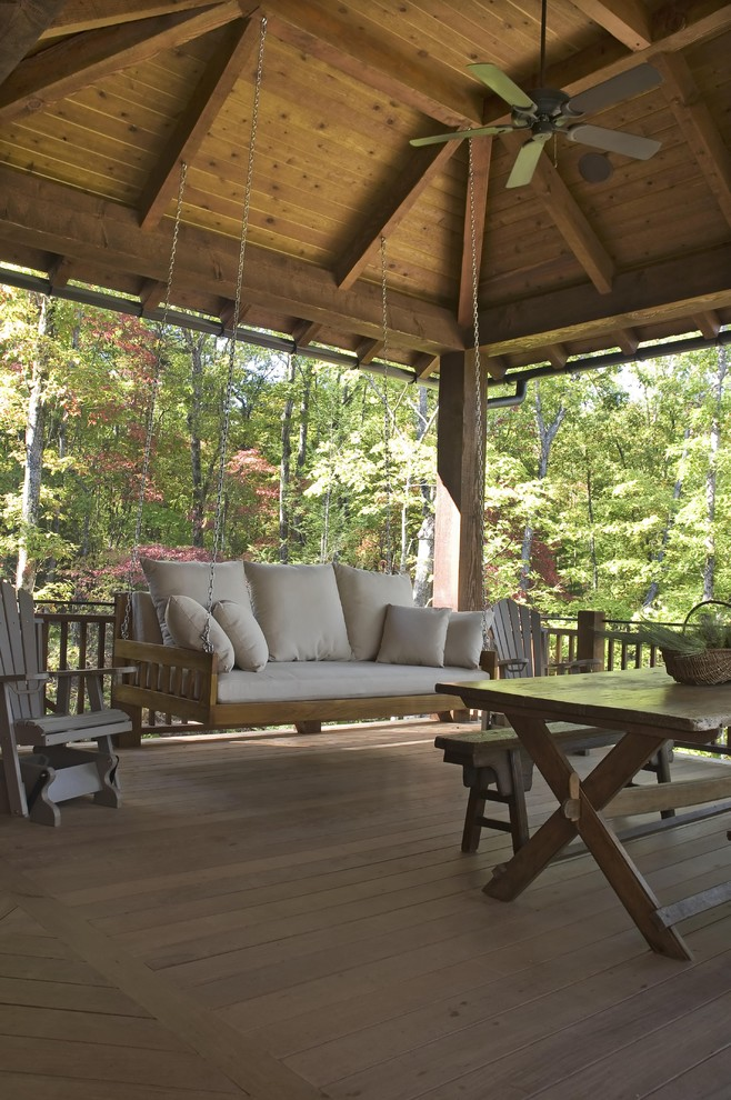 Large mountain style backyard deck photo in Other with a roof extension and a fire pit