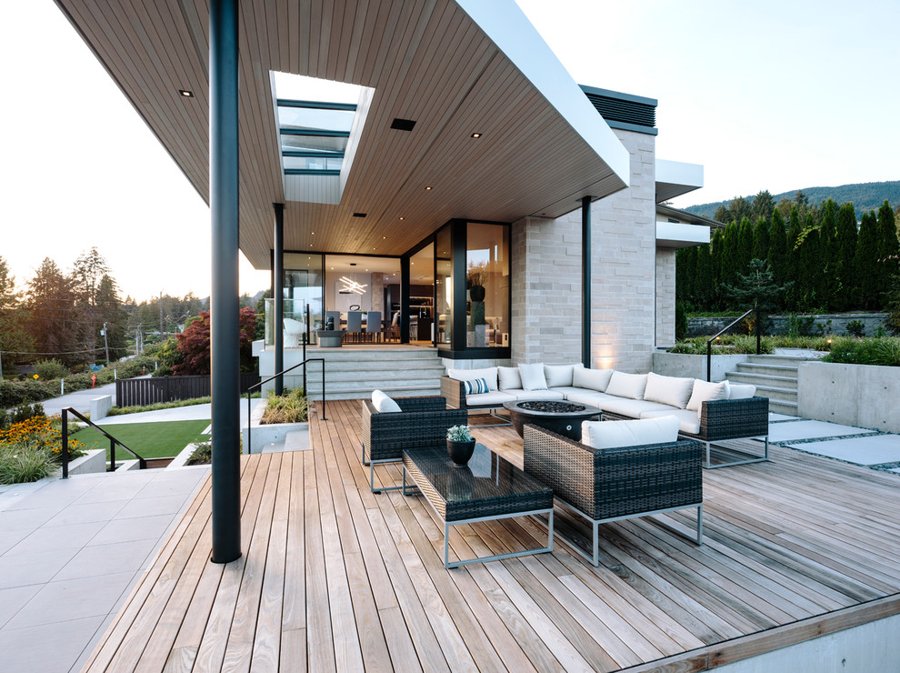 Large trendy deck photo in Vancouver with a roof extension