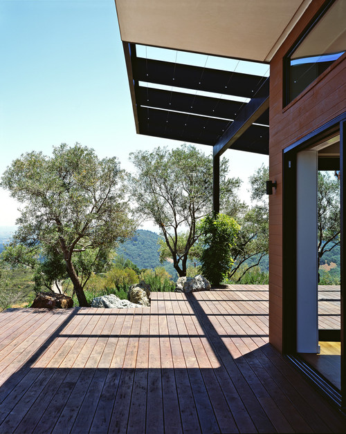 Wrapping around the outer edge of a hilltop house, this deck provides expansive views of the surrounding valley and hills. Bordering the home itself, it's an extension of the modern minimalist style.