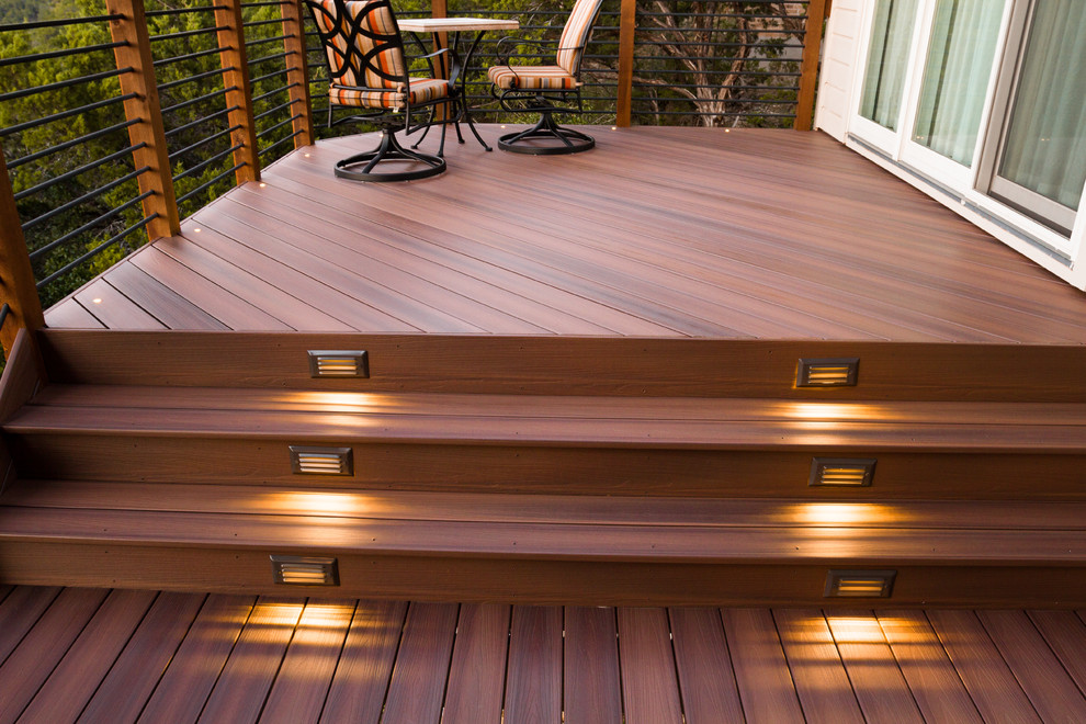 Example of a large classic backyard deck design in Austin with a roof extension