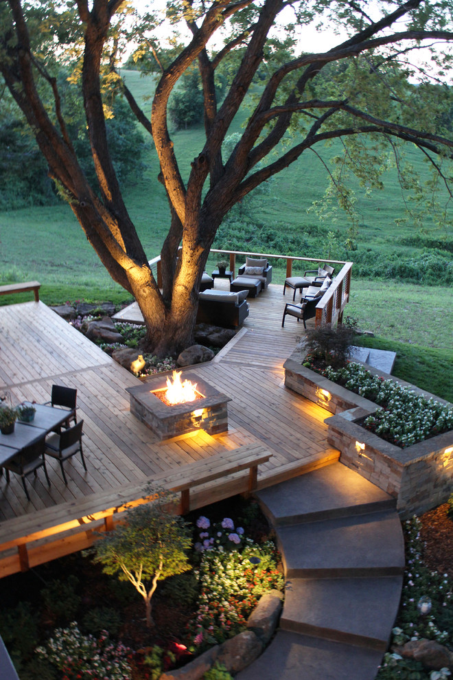 Example of a large trendy backyard deck design in Kansas City with a fire pit and no cover