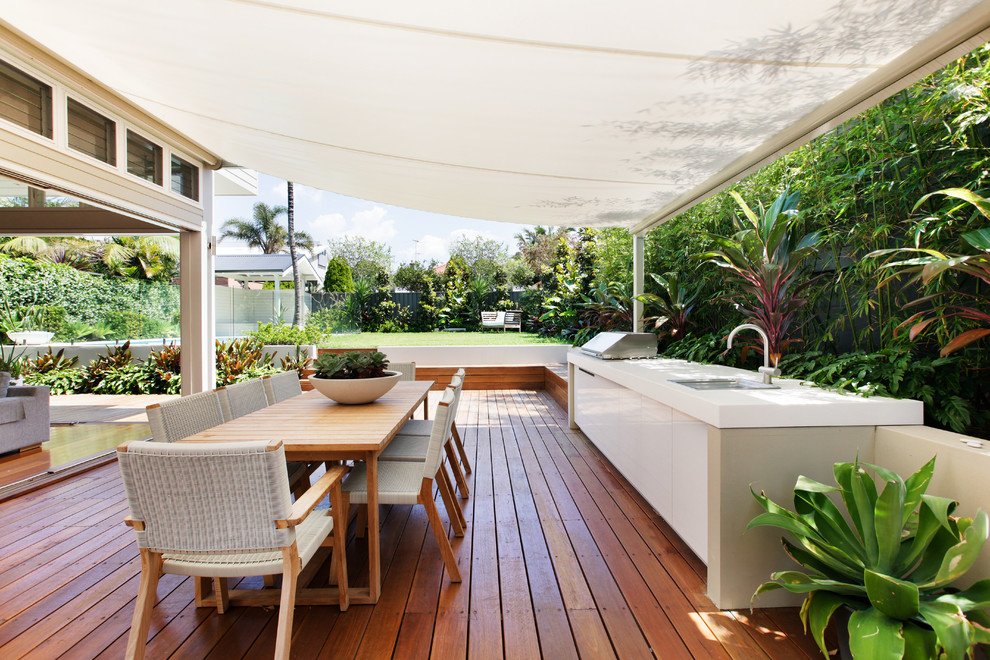 Example of a mid-sized transitional side yard outdoor kitchen deck design in Sydney with an awning
