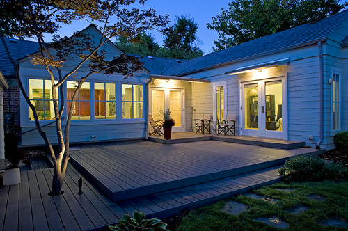 Multiple levels are crossed by this floating deck design, which runs right into the corner provided by the L-shaped house and extends deep into the yard, even encompassing a small tree.