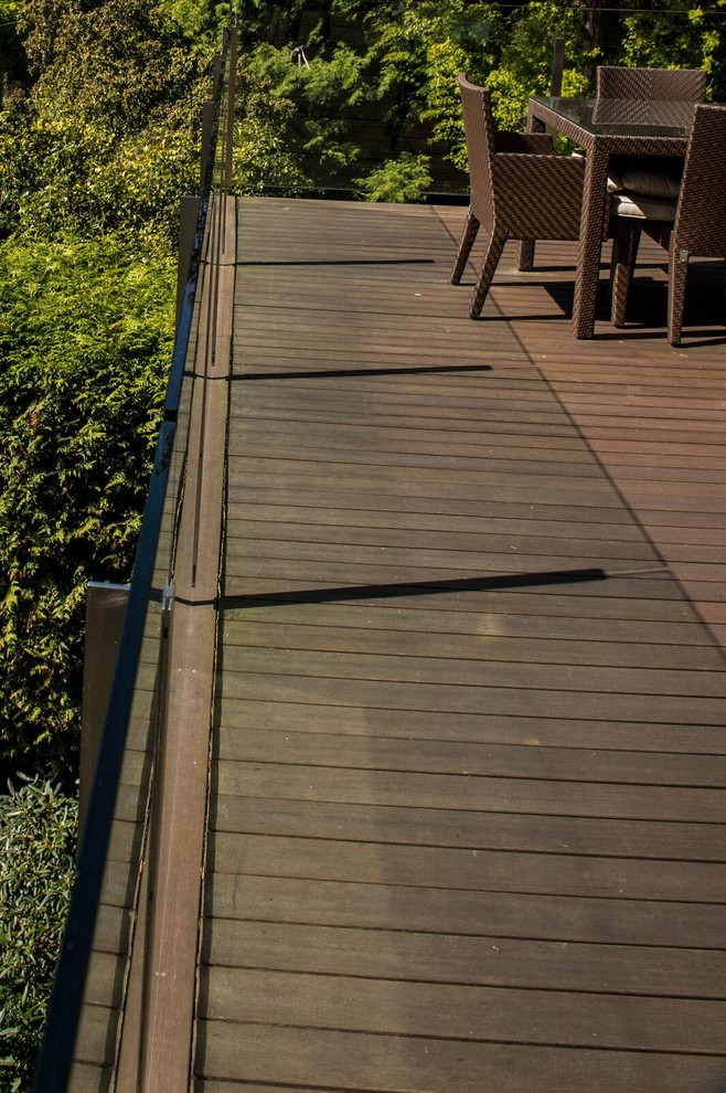 Example of a mid-sized trendy backyard deck design in Vancouver with a roof extension