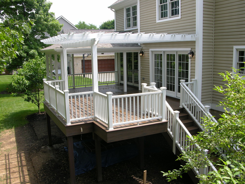 Large elegant backyard deck photo in Other with a pergola