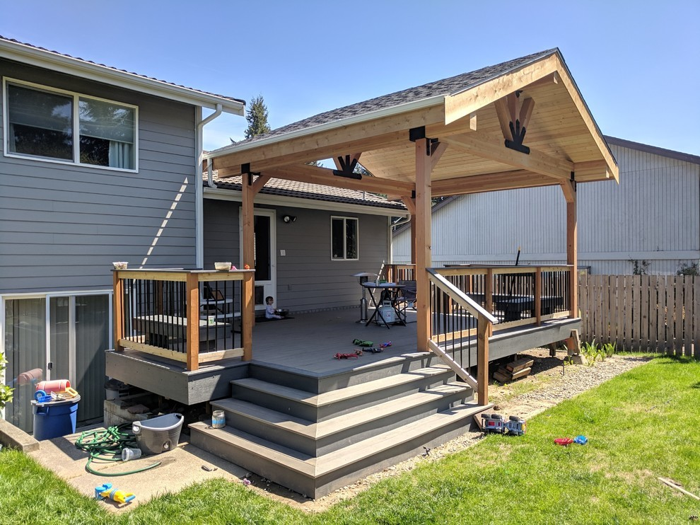 Large transitional backyard deck photo in Seattle with a pergola