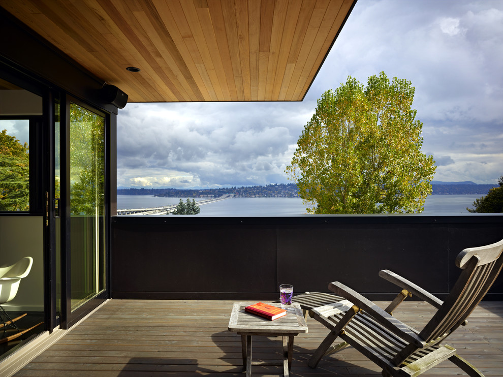 Mid-sized minimalist rooftop deck photo in Seattle with a roof extension