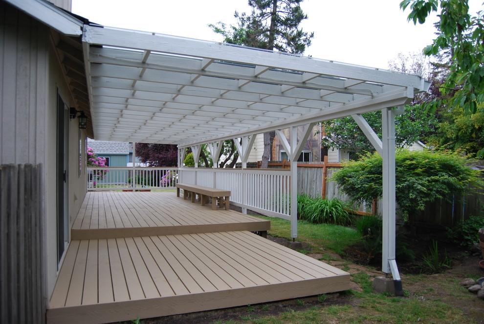 Large coastal backyard deck photo in Portland with a pergola
