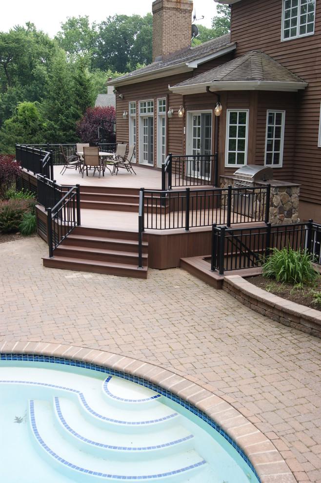 Large elegant backyard outdoor kitchen deck photo in New York
