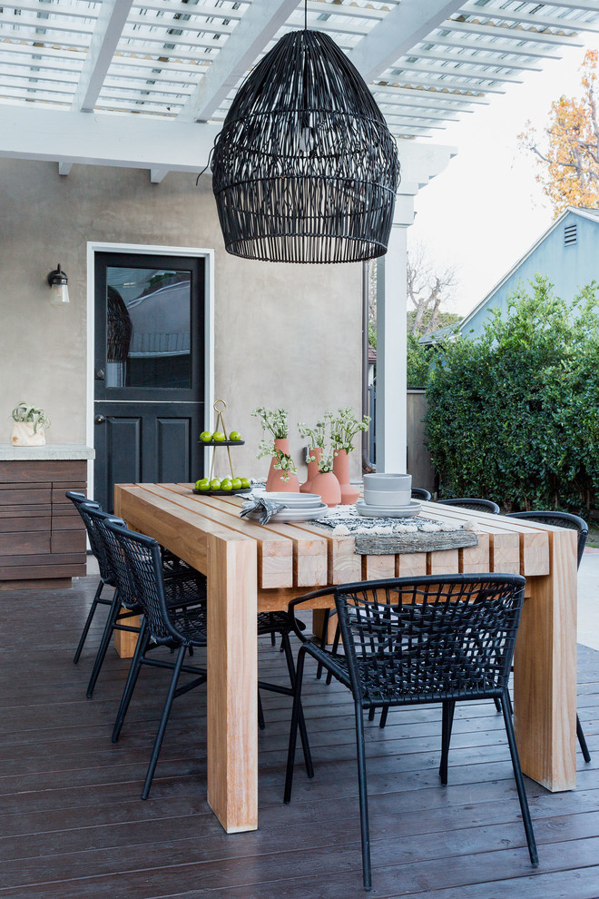 Example of a beach style deck design in Los Angeles with a pergola