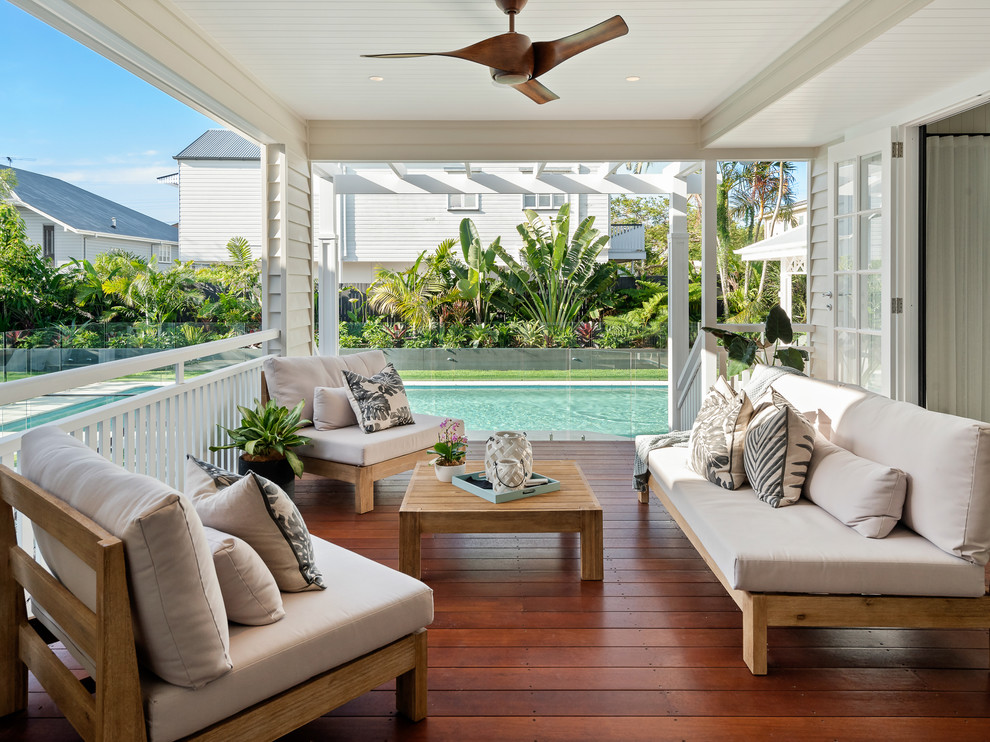 Design ideas for a mid-sized beach style backyard deck in Brisbane with a roof extension.