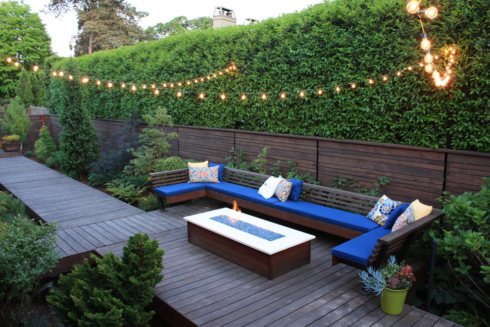 Mid-sized trendy backyard deck photo in Other with a fire pit