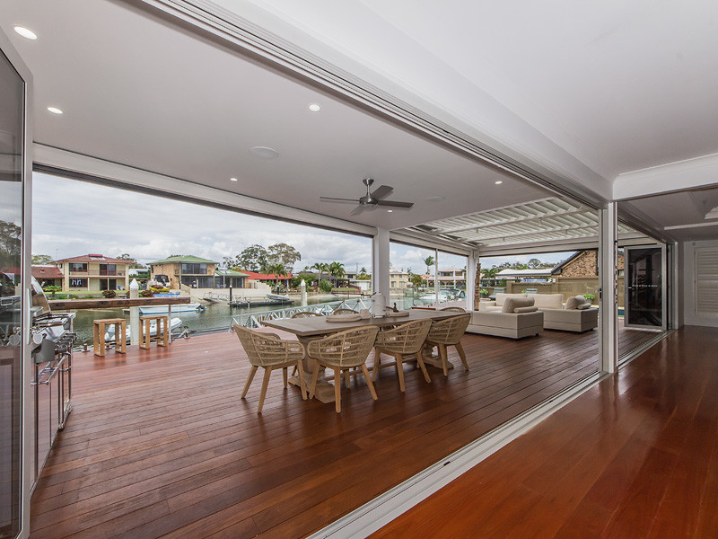 Photo of a large contemporary backyard deck in Brisbane with a roof extension.