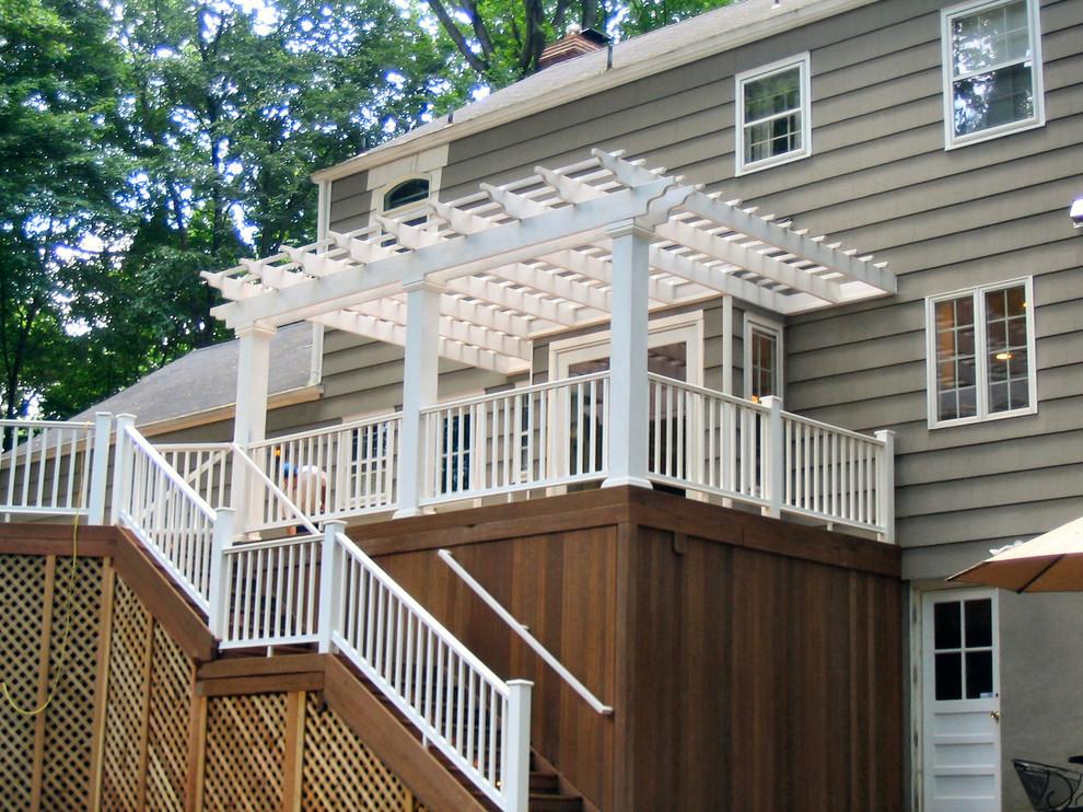 Large elegant backyard deck skirting photo in New York with a pergola