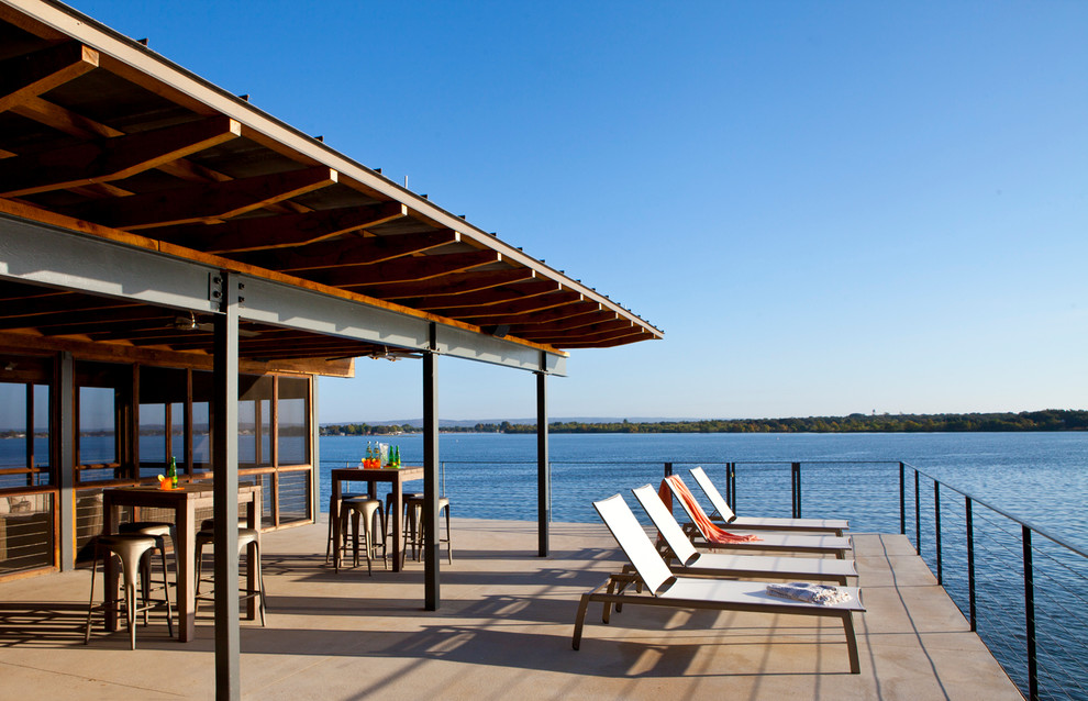 Inspiration for a contemporary backyard deck remodel in Austin with a roof extension