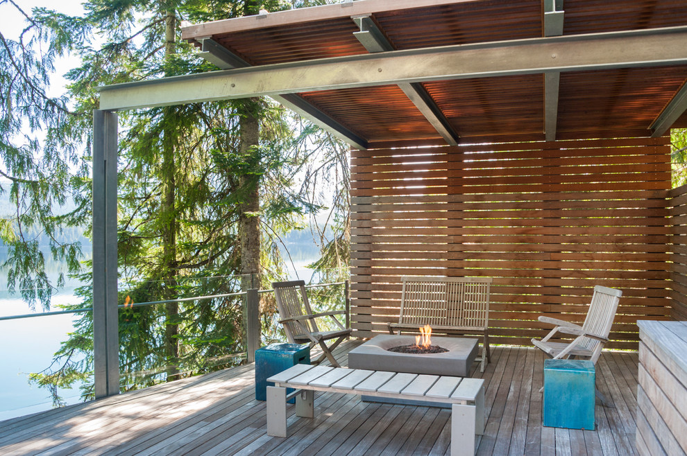 Mid-sized trendy backyard deck photo in Seattle with a fire pit and an awning