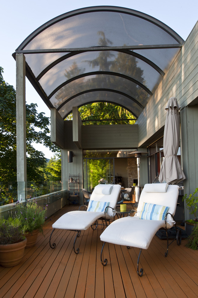 Example of a large minimalist side yard deck design in Vancouver with an awning