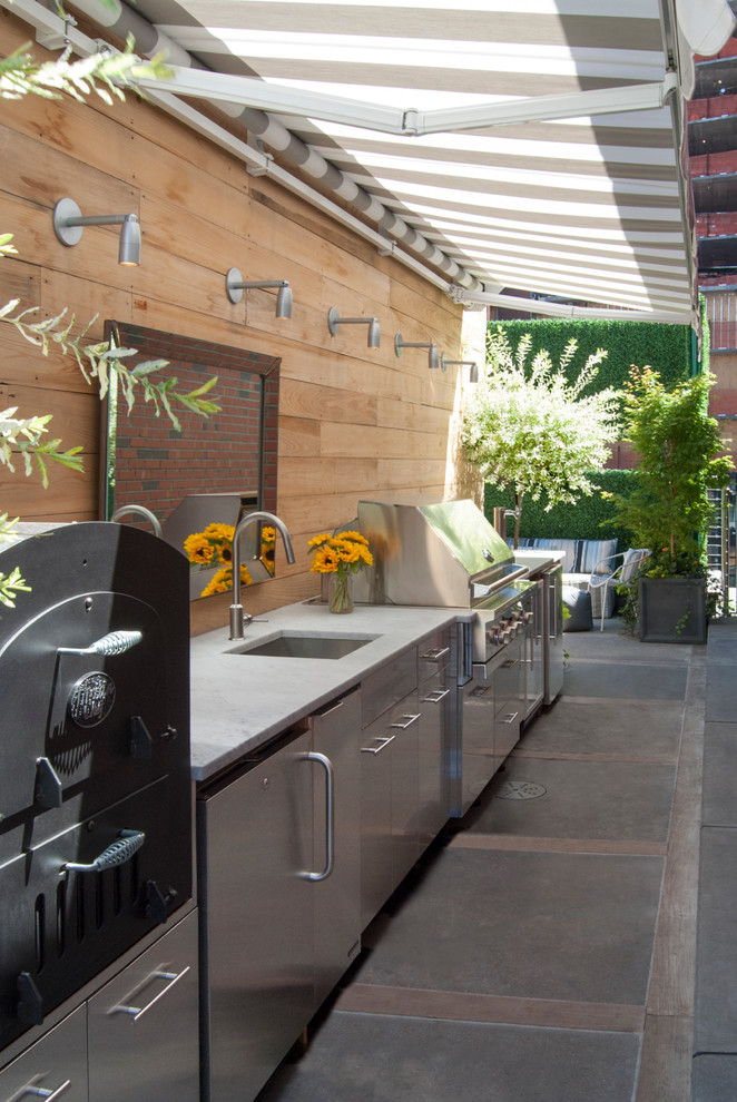 Inspiration for a large contemporary rooftop rooftop outdoor kitchen deck remodel in New York with an awning