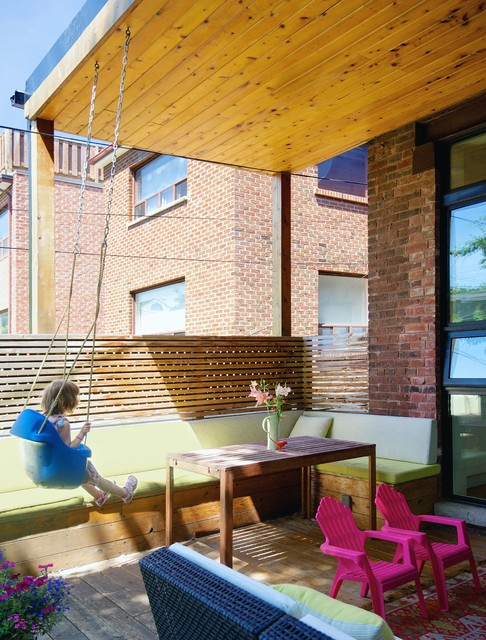 Example of a mid-sized transitional backyard deck design in Toronto with a roof extension