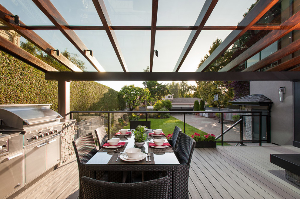 Example of a mid-sized trendy backyard deck design in Vancouver with a pergola