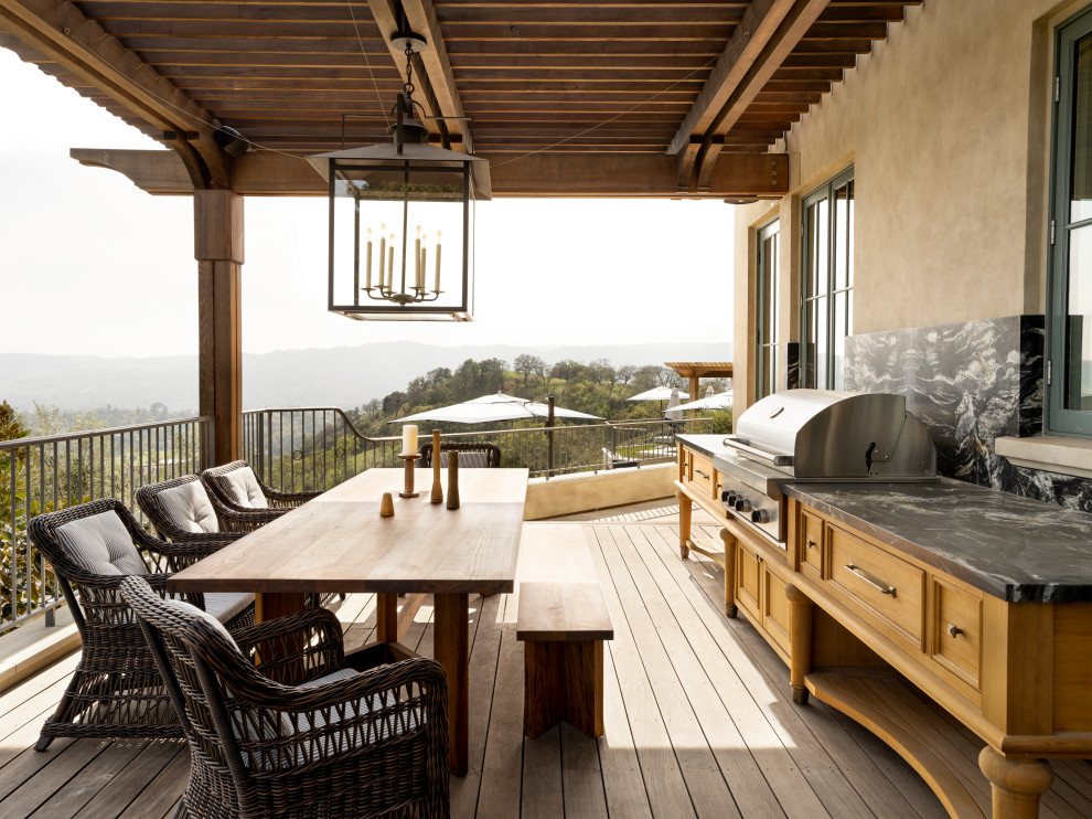 Example of a classic second story metal railing outdoor kitchen deck design in San Francisco with a roof extension