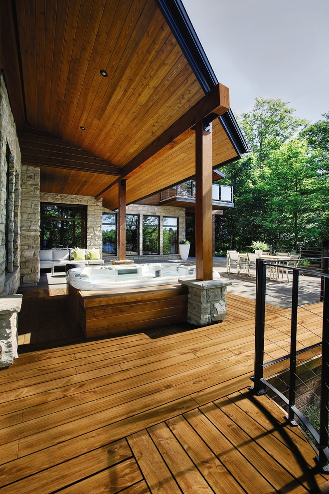 Trendy backyard deck photo in Other with a roof extension