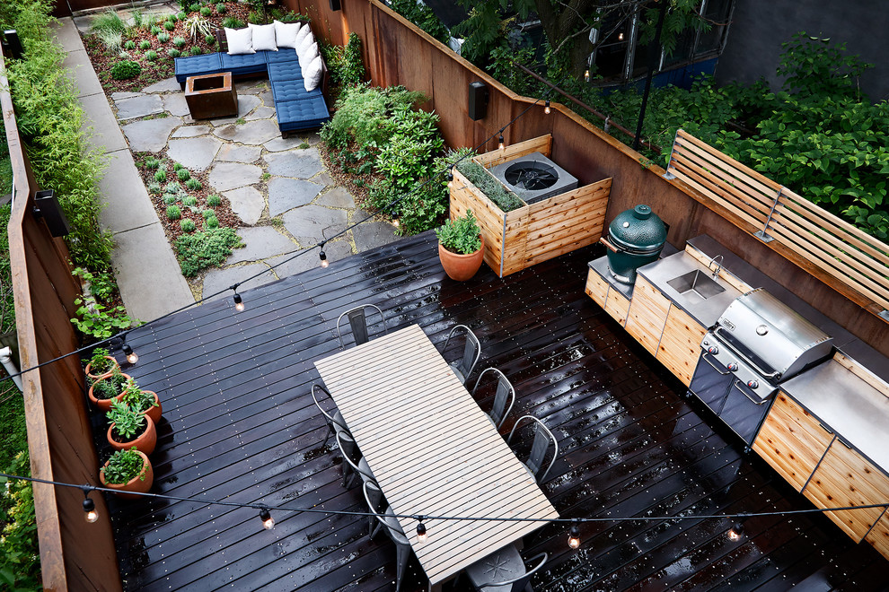 Example of a trendy backyard deck design in New York with a fire pit