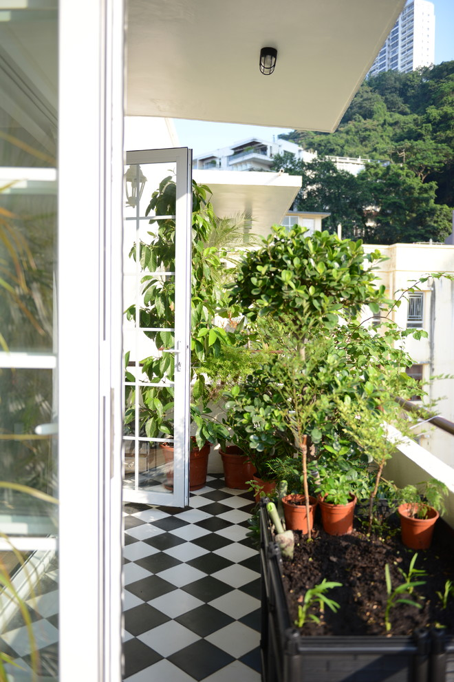 Example of a trendy deck container garden design in Hong Kong with a roof extension