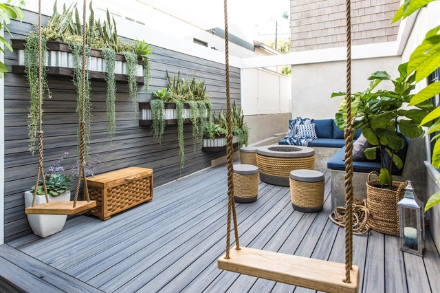 deck with hanging elevated plants that trail down and a bench swing