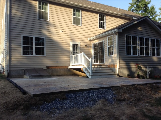 Small 8'x8' deck with enlarged stairs down to Stamped Concrete Patio