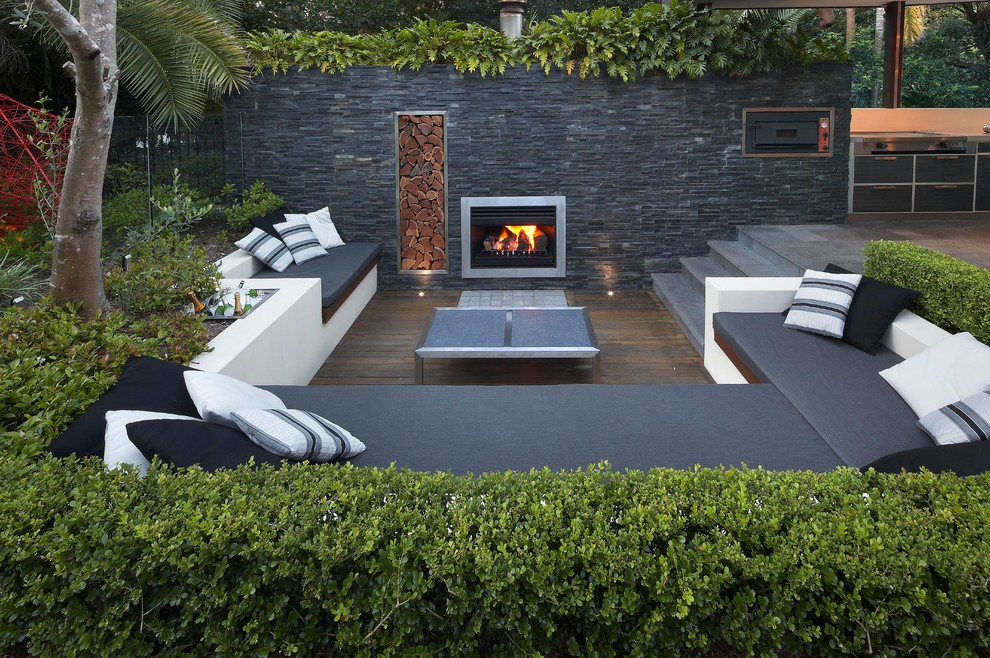 Example of a trendy backyard deck design in Sydney with a fire pit