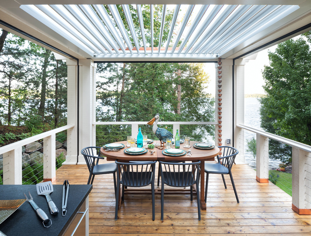 Large beach style backyard outdoor kitchen deck photo in Minneapolis with a pergola