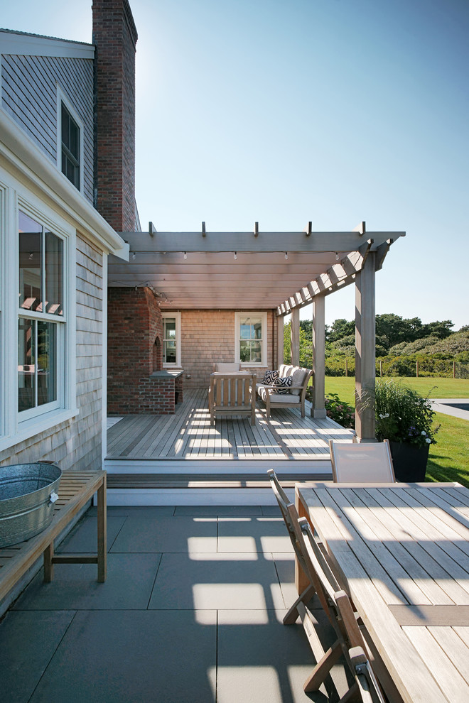 Inspiration for a coastal backyard deck remodel in Other with a fire pit and a pergola